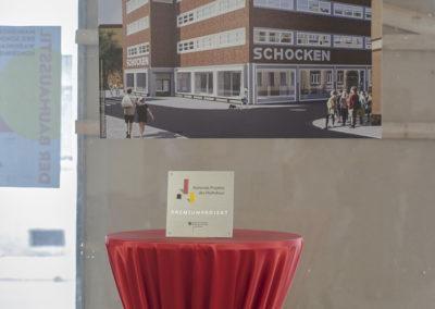 """Die Plakette """"Premiumprojekt"""" vor der Bildtafel mit den denkmalgerechten Wiederherstellung der Kaufhausfassade"""